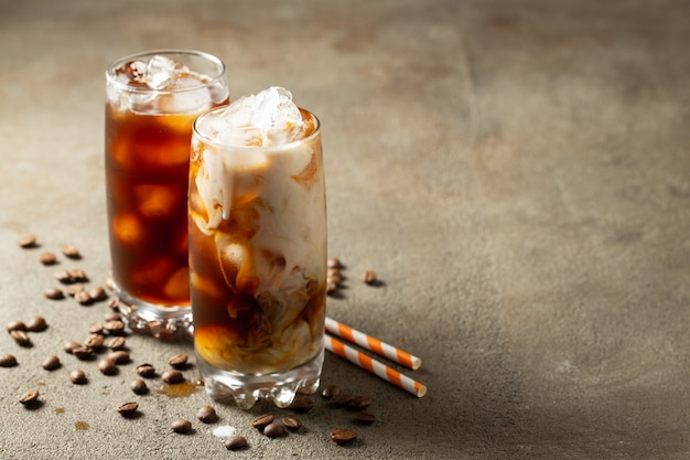 Ice coffee in a tall glass with cream poured over