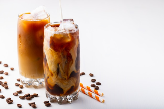 Ice coffee in a tall glass with cream.