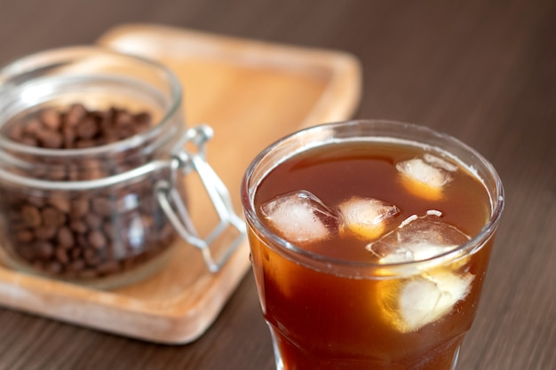 Ice coffee with ice cubes and jar with coffee beans on wooden plate. cold brew.
