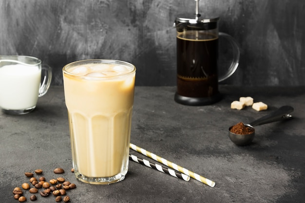 Ice coffee with milk in a tall glass on a dark background. copy space. food background