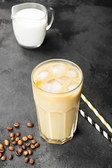 Ice coffee with milk in a tall glass on a dark background