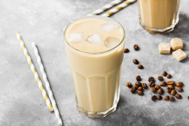 Ice coffee with milk in a tall glass on a gray background