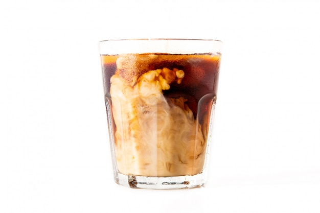 Ice coffee with milk on white wall