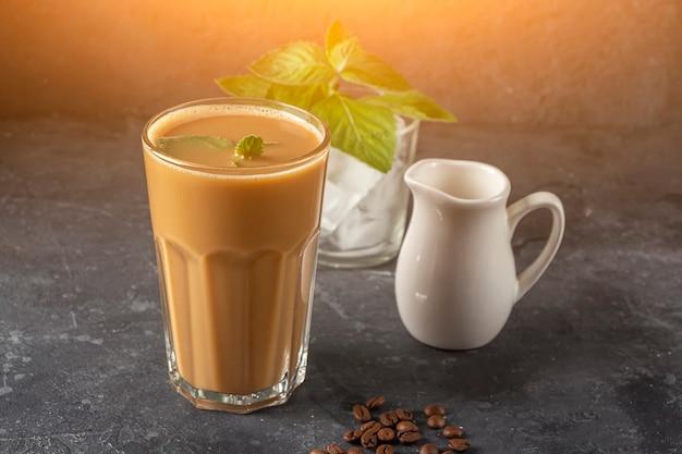 Ледяной кофе с мятой и молоком. большой стакан кофейного коктейля и стакан с кубиками льда. прохладный летний освежающий напиток на темном фоне в ключе закона. скопируйте место для текста.