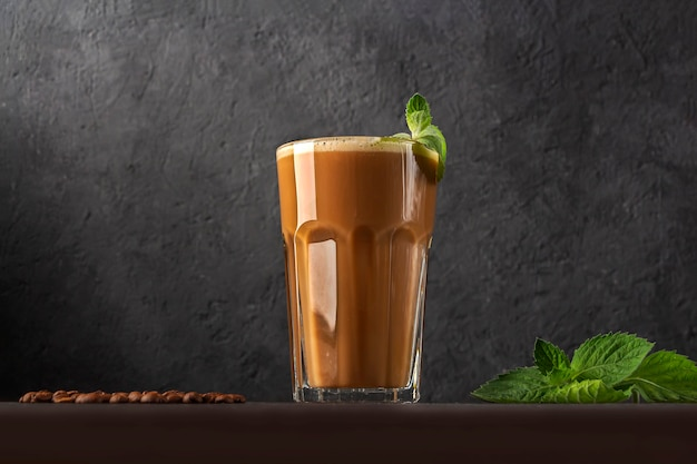 Ледяной кофе с мятой и молоком. большой стакан кофейного коктейля. прохладный летний освежающий напиток на темном фоне в ключе закона. скопируйте место для текста.