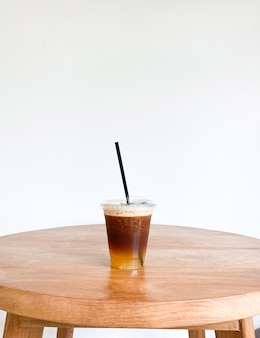 Ice coffee with orange juice in a plastic glass on the wooden table with copy space
