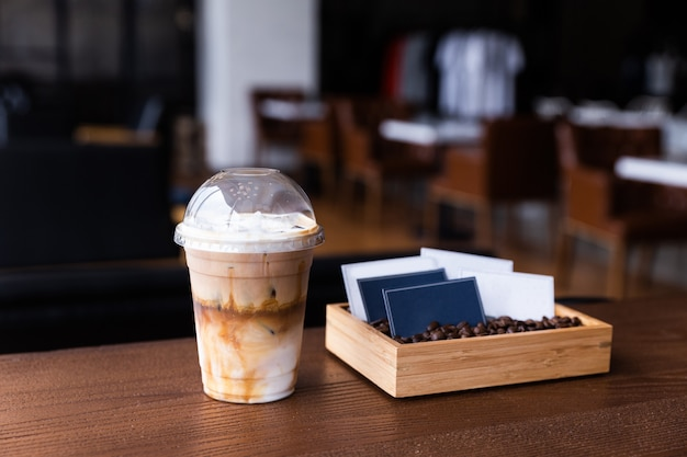 Ice coffee on a wood table with cream being poured into it shows the texture in a plastic cup, business cards in a wooden box filled with coffee beans