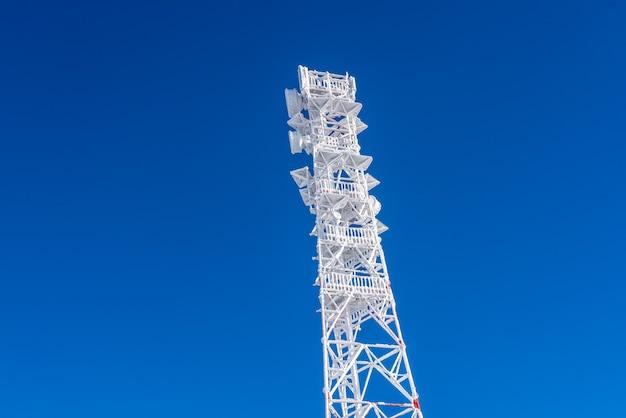 고지대에 위치한 기지국의 지붕에 얼음으로 뒤덮인 기지국. 휴대폰 스테이션.