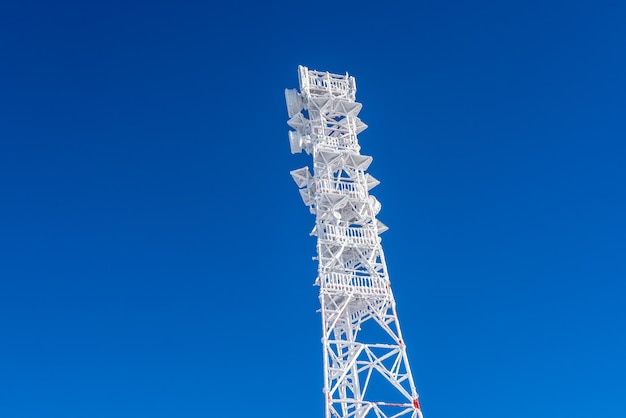 Ice-covered cell tower on the roof of the base radio station located in the highlands. cellular phone station.