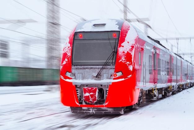 Покрытый льдом электропоезд мчится по размытому зимнему железнодорожному ландшафту