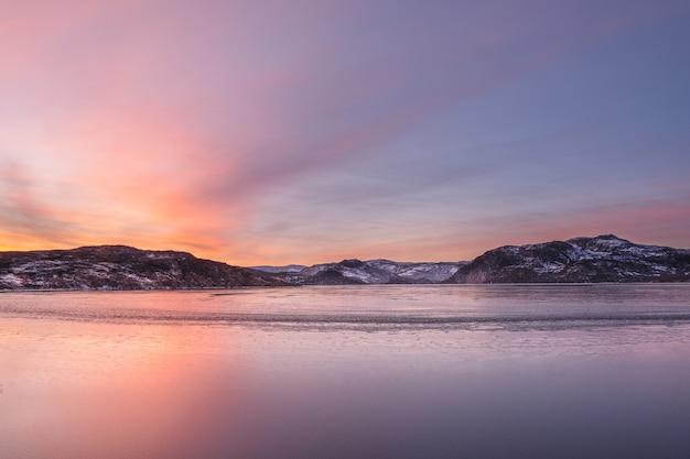 An ice-covered mountain lake. magic magenta sunset on a mountain north of the lake. kola peninsula.