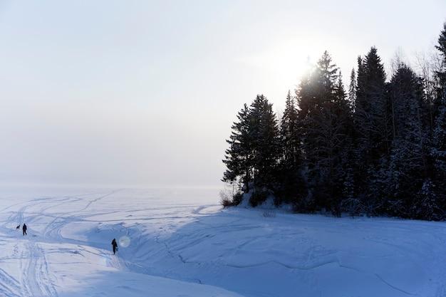 Покрытое льдом устье зимней реки, впадающей в озеро, в морозной дымке, с высоким берегом и людьми, идущими по льду