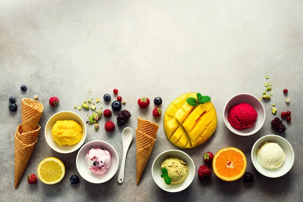 Ice cream balls in bowls, waffle cones, berries, orange, mango, pistachio on grey concrete . colorful collection, flat lay, summer concept, top view