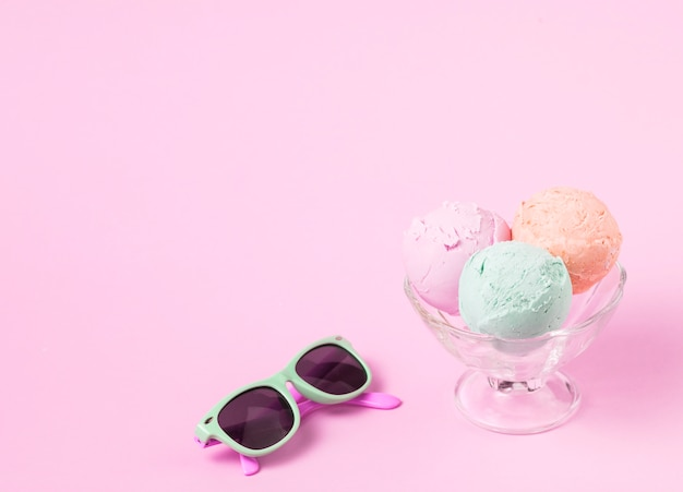 Ice cream balls on glass bowl near sunglasses