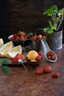 Ice cream balls of strawberries and melons in a ceramic cup. plant strawberries in a vintage cup