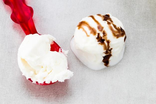 회색 배경에 초콜릿 소스가 있는 아이스크림 공, 위쪽 전망.