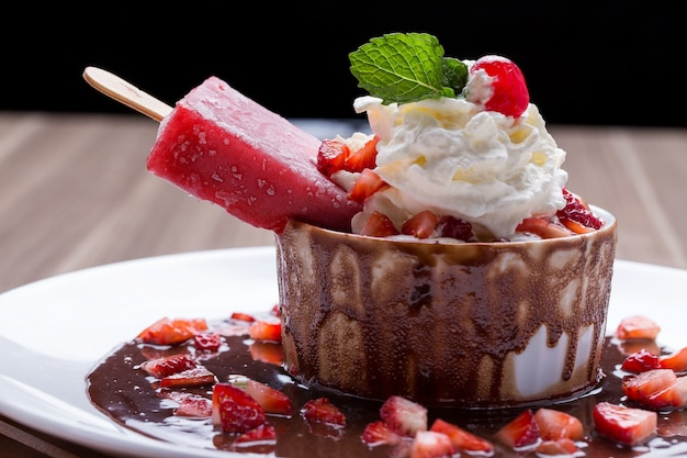 Ice cream in a bowl of dessert with chocolate, cream and strawberries