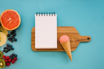 Ice cream concept with notepad on wooden board