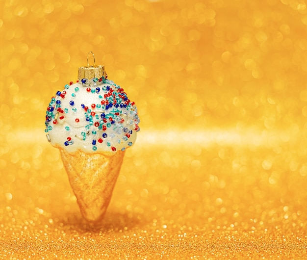 Ice cream cone on blurred golden bokeh background. copy space, selective focus. christmas ornaments