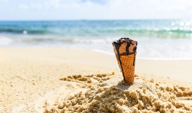 Ice cream cone on sand beach background - melting ice cream on beach sea in summer hot weather ocean landscape nature outdoor vacation , ice cream chocolate