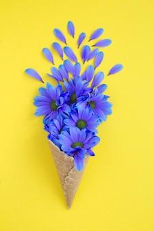黄色いテーブルの中央に青い花とアイスクリームコーン。上面図。春または夏の花のコンセプト。