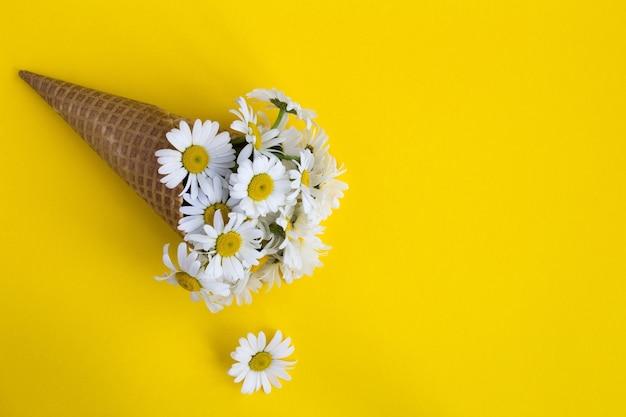 黄色のカモミールとアイスクリームコーン