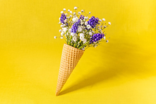 노란색 벽에 꽃과 아이스크림 콘입니다. 측면보기, 복사 공간, 봄 꽃 개념