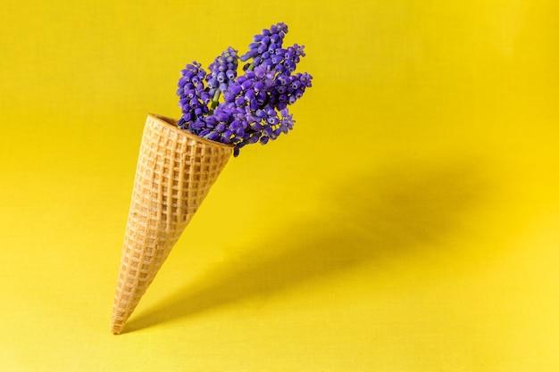 黄色の壁に花とアイスクリームコーン。側面図、コピースペース、春の花のコンセプト