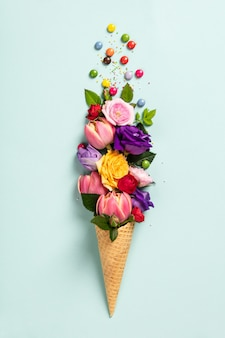 Ice cream cone with flowers and sprinkles summer minimal concept. Premium Photo