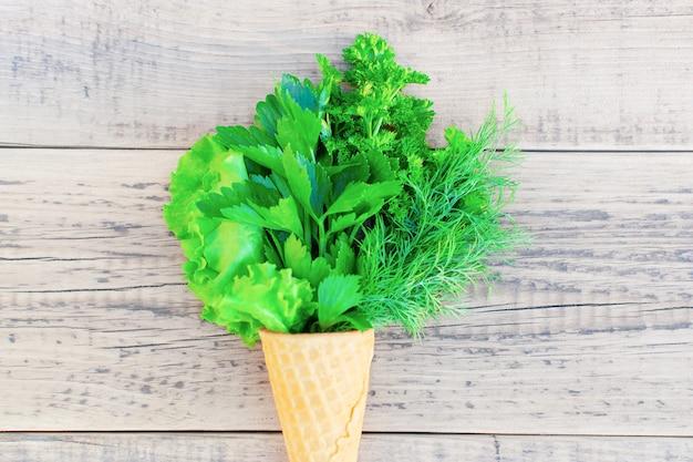 Конус мороженого со свежей зеленью на деревянном. салат, петрушка, укроп, цветок чеснока.