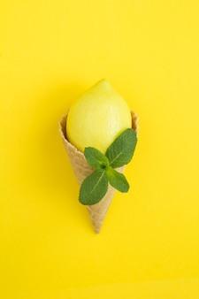 黄色の背景にレモンとミントのアイスクリームコーン。場所は垂直です。スペースをコピーします。