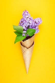 黄色の壁にライラックの花とアイスクリームコーン。春の花のワッフルカップ。ミニマリズムのファッションスタイル。コピースペース、フラットレイ