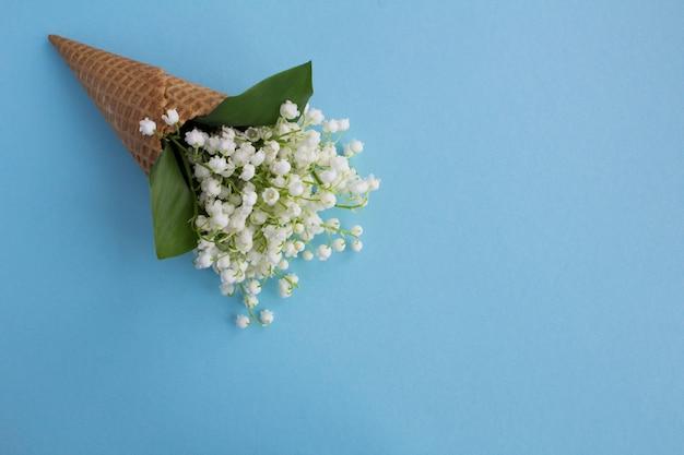 Конус мороженого с ландышами на синей поверхности. вид сверху. копирование пространства. концепция весенних цветов.