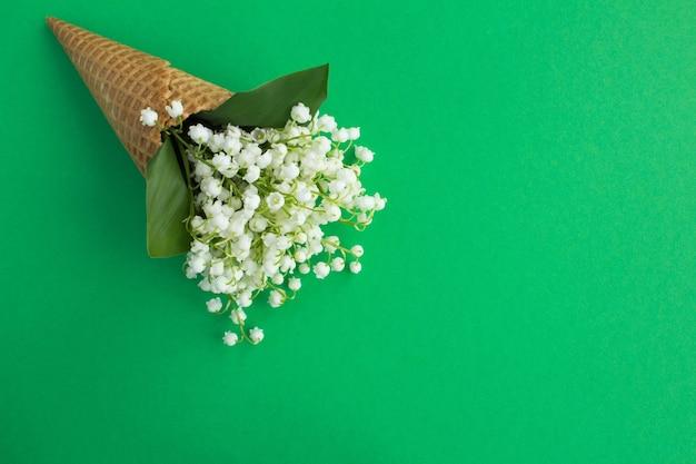 緑の背景にスズランとアイスクリームコーン