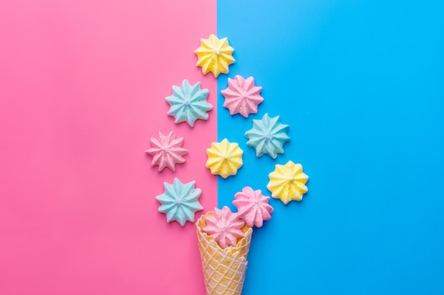 Ice cream cone with meringues on blue and pink