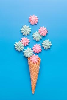 Ice cream cone with meringues on blue