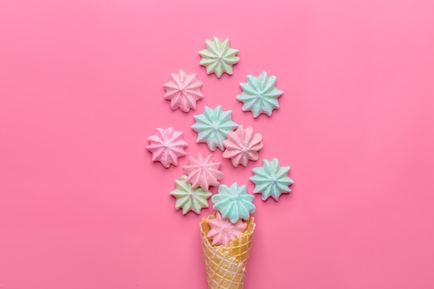 Ice cream cone with meringues on pink