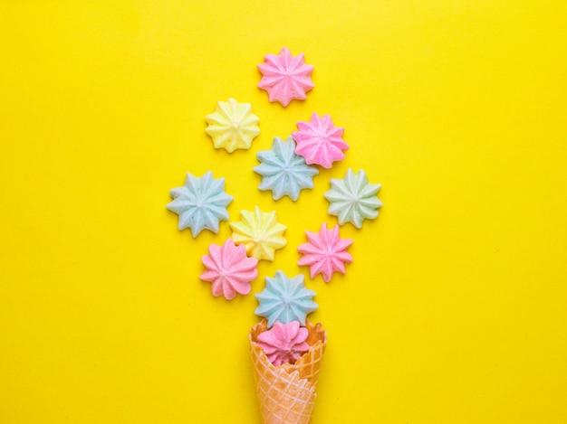 Ice cream cone with meringues on yellow