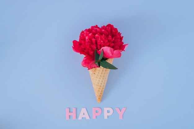 Ice cream cone with pink peony on blue, flat lay. happy text