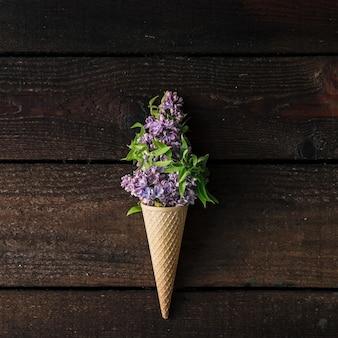 木製の壁に紫色のライラックとアイスクリームコーン。フラットレイ。夏のコンセプト。