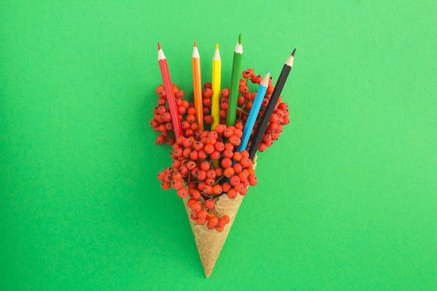 緑の表面に赤いナナカマドと色とりどりの鉛筆が付いたアイスクリームコーン。上面図。スペースをコピーします。