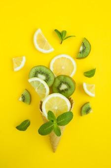 黄色の背景にスライスしたレモンとキウイのアイスクリームコーン。場所は垂直です。