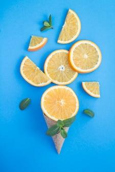 青い背景にスライスしたオレンジ色のフルーツとアイスクリームコーン。場所は垂直です。