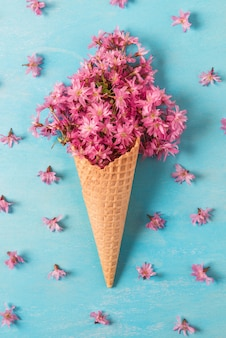 Ice cream cone with spring blossom pink cherry or sakura flowers. flat lay. top view. vertical orientation