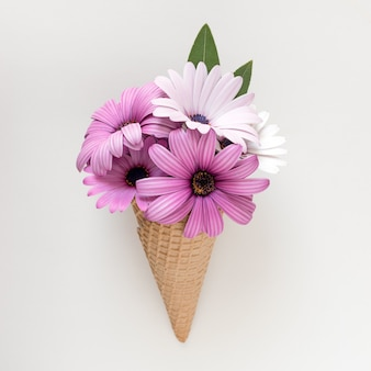白い背景の上の春の花とアイスクリームコーン