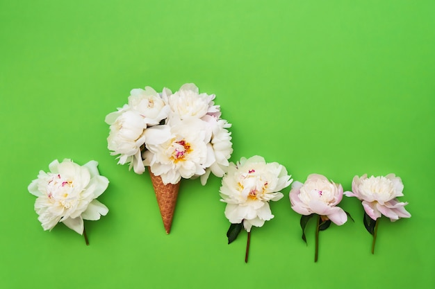 Ice cream cone with white peony flowers around on green background.