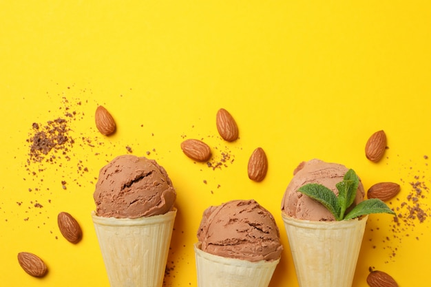 Ice cream in cones and almond on yellow surface. sweet food