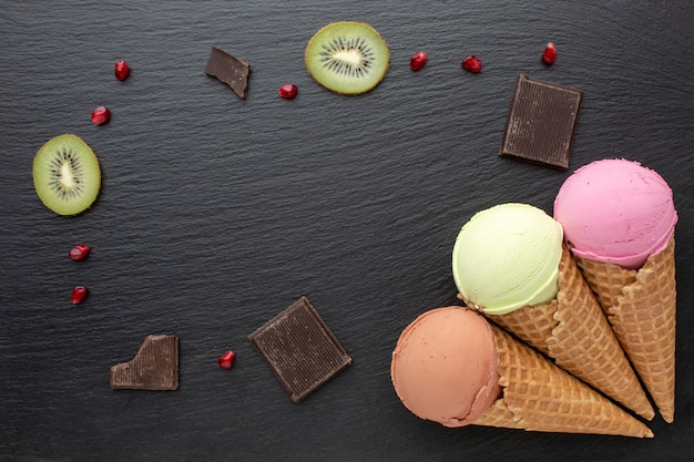 Ice cream on cones with chocolate and kiwi on table