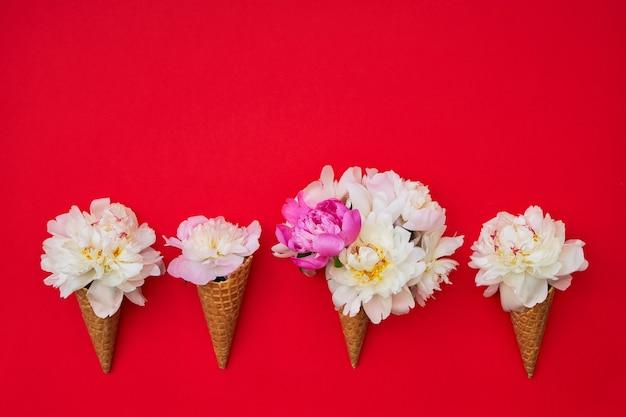 Конусы мороженого с белыми цветами пиона на красном столе. летняя концепция. копировать пространство, вид сверху