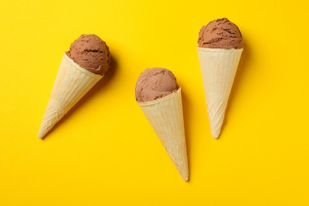 Ice cream in cones on yellow surface. sweet food